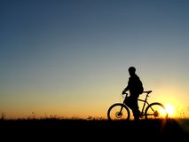 Cycling. Mountain biker girl silhouette in sunrise royalty free stock photography