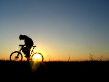 Cycling. Mountain biker girl silhouette in sunrise Royalty Free Stock Photos