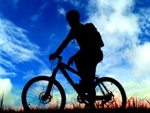 Cycling. Mountain biker silhouette and blue sky Stock Images