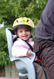 Cycling. Little girl in the seat bicycle with a helmet on his head Stock Images