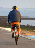 Cycling. A cyclist on a seashore path stock image