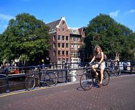 Cycling across canal bridge, Amsterdam. Stock Photo
