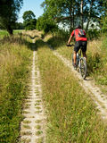 Cycling along agricultural track Royalty Free Stock Image