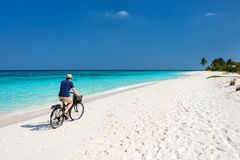 Cycling along tropical beach. Back view of young man bicycling along tropical beach at Maldives royalty free stock photography