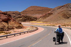 Cycling through Argentina. Woman cycling on the empty road in the remote part of north west Argentina Royalty Free Stock Photo