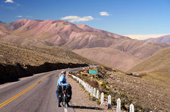Cycling through Argentina. Woman cycling on the empty road in the remote part of north west Argentina Stock Images