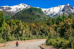 Cycling through the argentinian mountains. Woman cycling on the corrugated road through the mountains in Lake District, Argentina Stock Image