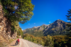 Cycling through the argentinian mountains. Woman cycling on the corrugated road through the mountains in Lake District, Argentina Royalty Free Stock Image