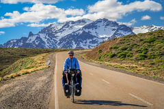 Cycling through the argentinian mountains. Woman cycling on the paved road through the mountains, Argentina Royalty Free Stock Photo