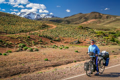 Cycling through the argentinian mountains. Woman cycling on the paved road through the mountains, Argentina Stock Image