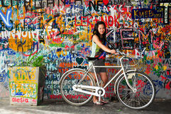 Cycling. Asian girl with bicycle in front of art deco wall Stock Photos