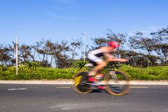 Cycling Athlete Motion Speed Blur Close-Up Action. Athlete cycling motion speed blur close-up action morning road course second leg of triathlon race stock image