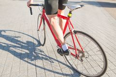 Cycling athlete`s foot and red bike close-up. Man rides the city on a bicycle. Sports concept stock images