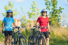Cycling Athlets Exercising Relaxing During their Exercise in Nat. Caucasian Cycling Athlets Exercising Relaxing During their Exercise in Nature Environment Stock Photography