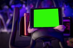 A cycling bike with a green screen tablet on a towel in a dark blue room with LED lighting stock photos