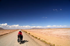 Cycling through Bolivia. Woman cycling on the remote road in rural part of Boliviarn Royalty Free Stock Image