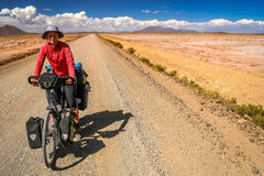 Cycling through Bolivia. Woman cycling on the remote road in rural part of Bolivia Royalty Free Stock Photos
