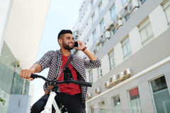 Cycling and calling. Smiling young Indian man on bicycle calling on the phone Stock Image