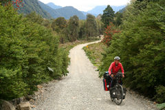 Cycling on Carretera Austral. Cyclist climbing up the fill on the Carretera Austral, southern Patagonia, Chile Royalty Free Stock Images