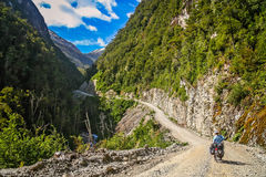 Cycling on Carretera Austral. Cyclist climbing up the hilly road on the Carretera Austral, southern Patagonia, Chile Royalty Free Stock Photo