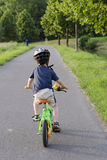 Cycling child. Child cycling on a cycle path in nature, back view Royalty Free Stock Images