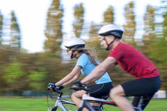 Cycling Concept: Young Caucasian Couple Having a Sppedy Bicycle Stock Photography