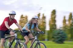 Cycling Concept: Young Caucasian Couple Having a Sppedy Bicycle Royalty Free Stock Images