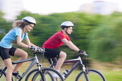 Cycling Concept: Young Caucasian Couple on Speedy Trip Royalty Free Stock Image