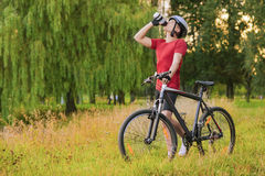 Cycling Concept: Young Caucasian Male Cyclist Having water Break Stock Images