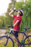 Cycling Concept: Young Caucasian Male Cyclist Having water Break Stock Photos
