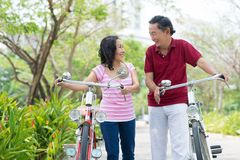 After cycling. Copy-spaced image of happy seniors carrying their bicycles in the park royalty free stock photography