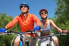Cycling couple. Young smiling couple cycling through summer park Royalty Free Stock Photos