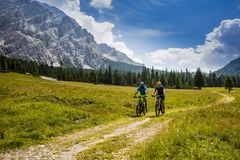 Cycling couple with bikes on track, Cortina d`Ampezzo, Dolomites royalty free stock photo