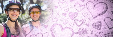 Cycling Couple with valentine`s love transition hearts. Digital composite of Cycling Couple with valentine`s love transition hearts stock photo