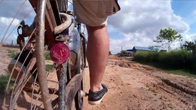Cycling down an unpaved muddy sunny dirt lane in rural Southeast Asia. With various small houses and village structures - rear mounted action cam reveals road stock video