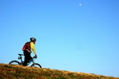 Cycling downhill. Man riding his bike alone and white moon on the sky Royalty Free Stock Image