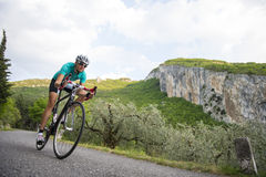 Cycling downhill - woman with road bike in full speed. Girl with her road cycle in full action Stock Photo