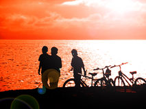 Cycling and fishing. Teenagers go cycling and fishing on the beach Royalty Free Stock Images