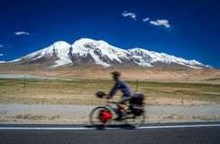 Cycling in front of Muztagh Ata Stock Images