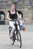 Cycling girl on Amsterdam Dam Square. AMSTERDAM-AUG. 19, 2012. Cycling girl on Aug. 19 in Amsterdam. 38% of traffic movement in the city is by bike , 37% by car Stock Image