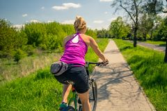 Cycling girl on mountain bike in city park, summer day Royalty Free Stock Images