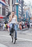Cycling girl at Rokin, Amsterdam. AMSTERDAM-AUG. 19, 2012. Cycling girl on Aug. 19 in Amsterdam. 38% of traffic movement in the city is by bike , 37% by car, 25 Stock Images