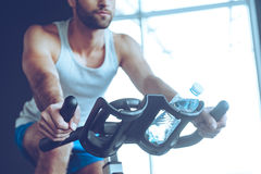 Cycling at gym. Part of low angle view of young man in sportswear cycling at gym Royalty Free Stock Images