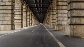 Cycling lanes running between arches of Pont de Bercy in Paris, time-lapse. Stock footage stock footage
