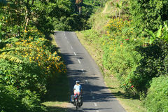 Cycling through Lombok. Female cyclist cycling through tropics in Lombok, Indonesia Stock Photo