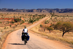 Cycling in Madagascar. Woman cycling  towards Parc National Isalo in Madagascar Royalty Free Stock Image