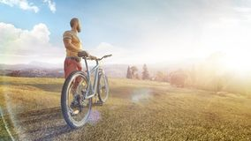 Free Cycling. Man With Bike On A Forest Road In The Mountains On A Summer Day. Mountain Valley During Sunrise. Sport Stock Image - 163783641