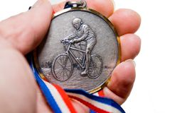 Cycling Medal / Award. Hand holding a medal from a bicycle race Stock Photo
