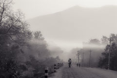 Cycling in the mist. People cycling in the morning mist in the lower parts of  the mountains in southern Nepal Royalty Free Stock Photos