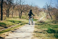 Cycling in nature. Rear view young woman stock image